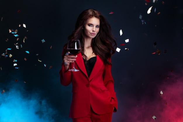 Het portret van mooie vrouw in rood kostuum houdt wijnglas terwijl status onder dalende heldere confettien
