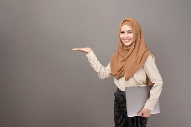 Het portret van mooie vrouw met hijab houdt computerlaptop op grijs