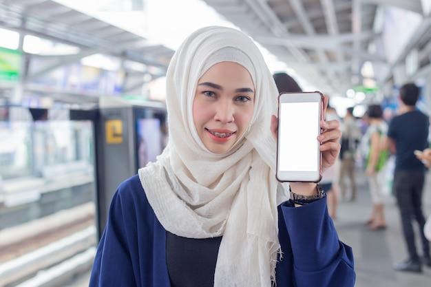 Het portret van moslimvrouwen gekleed in hijab, toont lege vertoning van smartphone.