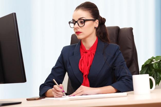 Het portret van onderneemster met laptop schrijft op een document op haar kantoor