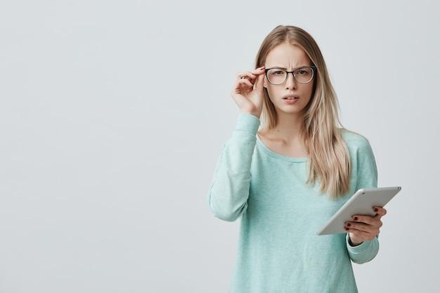 Het portret van ontevreden vermoeide jonge mooie onderneemster met blond haar in bril bevindt zich tegen grijze muur, werkt bij nieuw project op tablet, wil rust hebben. negatieve emoties en gevoelens