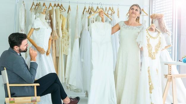 Het portret van paarliefde of bruid in huwelijksstudio terwijl probeer kostuum en kleding met boeketbloemen te kleden aangezien de romantische mensenconceptie in huwelijksmanier binnenlandse studio omhoog kleden.