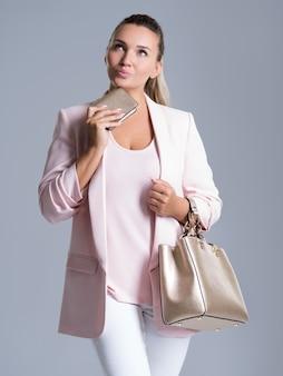 Het portret van peinzende vrouw met in hand handtas en een handtas overhandigt binnen wit