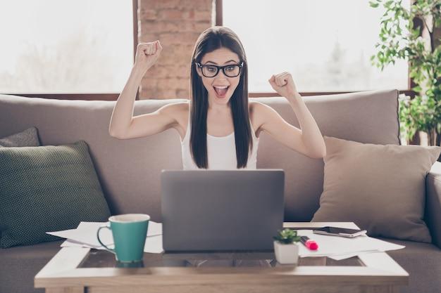 Het portret van positieve het huislaptop van het meisjeswerk heft vuisten op schreeuw ja