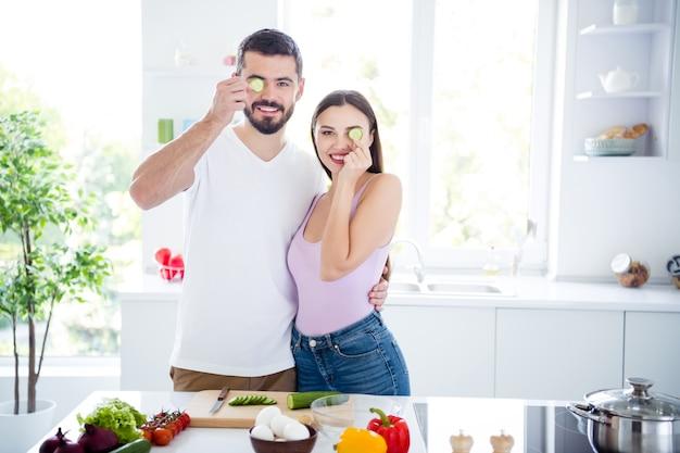 Het portret van positieve twee mensen omhelst dicht het voedselplak van dekkingogen