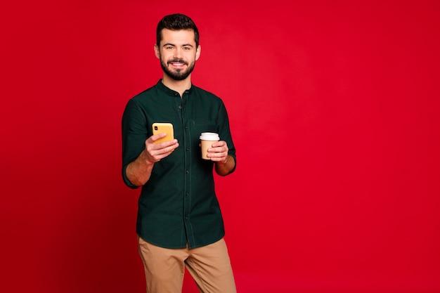 Het portret van positieve vrolijke kerelgreep haalt hete cafeïnedrank gebruikt zijn mobiel leest sociale media nieuws draagt groen overhemd bruine broekbroek
