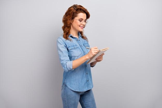 Het portret van positieve vrolijke slimme gerichte vrouw schrijft voorbeeldenboek middelbare schoolrapport draag vrijetijdskleding die over grijze kleurenmuur wordt geïsoleerd