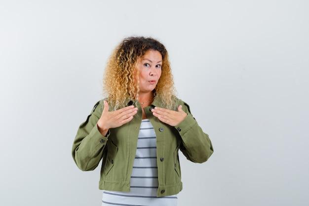 Het portret van prachtige vrouw die overhandigt borst in groen jasje, overhemd en verbaasd vooraanzicht kijkt