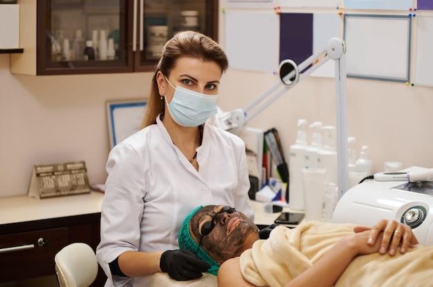 Het portret van schoonheidsspecialiste arts met patiënt op voorgrond