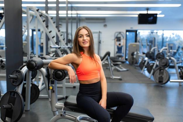 Het portret van slanke knappe jonge vrouw ontspant in gymnastiek na harde opleiding