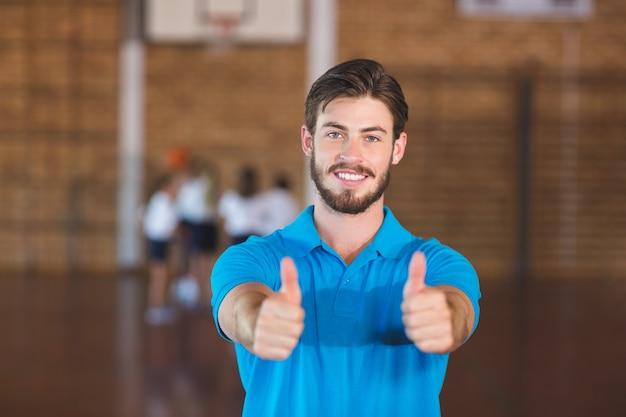 Het portret van sportenleraar het tonen beduimelt omhoog