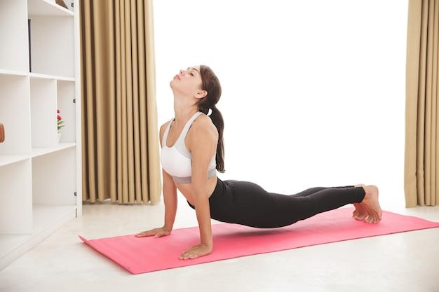 Het portret van sportief meisje dat yoga doet stelt thuis