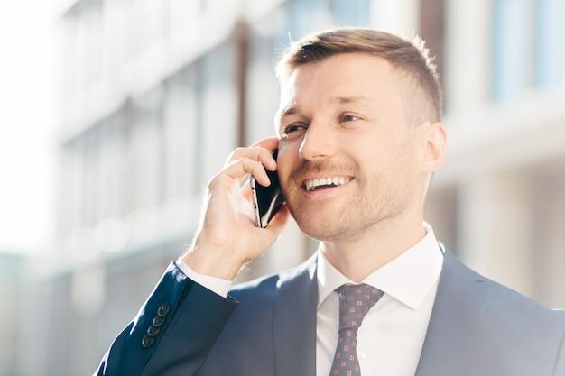 Het portret van succesvolle positieve zakenman heeft telefoongesprek, kijkt gelukkig