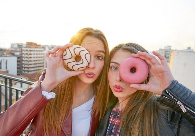 Het portret van tienermeisjes met donuts in oog dat pret heeft