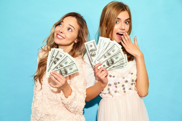 Het portret van twee gelukkige opgetogen blonde vrouwen die zich de zomerkleren verheugen verheugen zich en het houden van contant geldgeld dat over blauwe muur wordt geïsoleerd