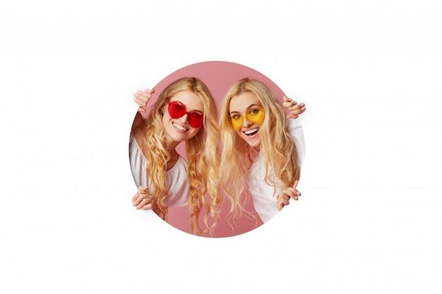 Het portret van twee jonge gelukkige, geschokte vrouwen in de zonnebril van de hartvorm kijkt door het witte gat in de muur. grote uitverkoop. grappige gezichten. lege ruimte voor tekst