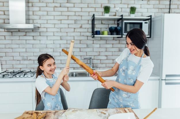 Het portret van twee meisjeszusters in de keuken kookt en besteedt hun tijd grappig elke dagconcept
