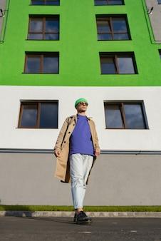 Het portret van volledige lengte van een man in vrijetijdskleding staat tegen een witgroen gebouw, kijkt naar de zon.