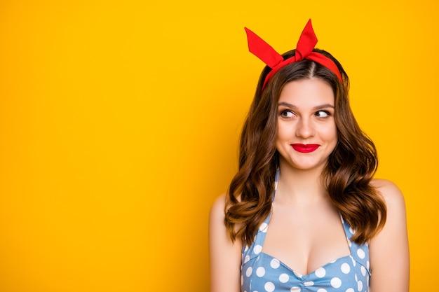Het portret van vrij charmant meisje kijkt exemplaarruimte over gele achtergrond