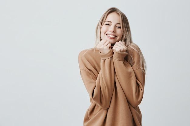 Het portret van vrij jonge blondevrouw heeft dromerige vrolijke uitdrukking, die losse warme sweater dragen