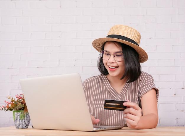 Het portret van vrij jonge vrouwen winkelt online en betaalt met creditcard.