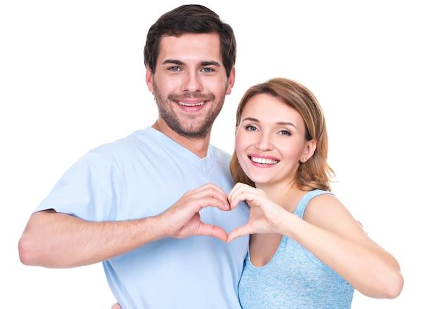 Het portret van vrolijk glimlachend paar die zich verenigen toont geïsoleerd handenhart -