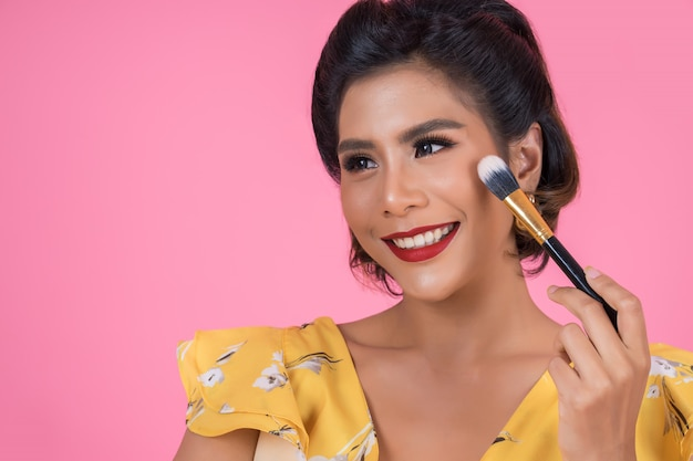 Het portret van vrouw met professionele make-upborstel toont