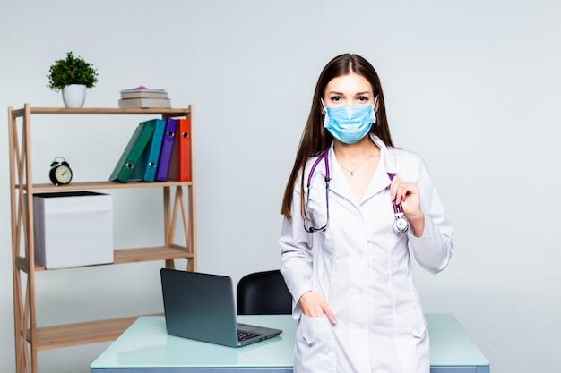 Het portret van vrouwelijke geneeskundetherapeutist arts die zich met handen bevinden kruiste op haar stethoscoop van de borstholding in bureau. medische hulp of verzekering concept.