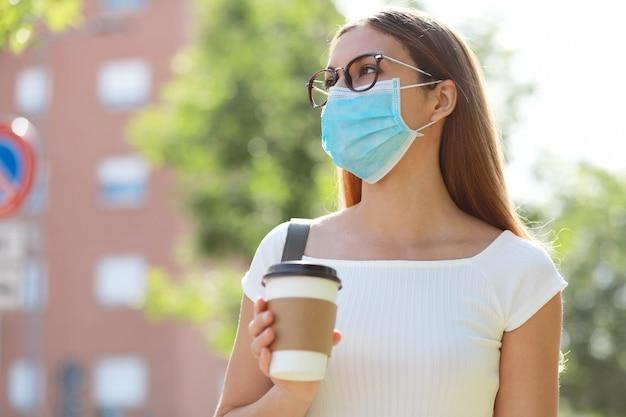 Het portret van vrouwelijke student die chirurgisch masker dragen die in de holding van de stadsstraat lopen haalt koffie weg