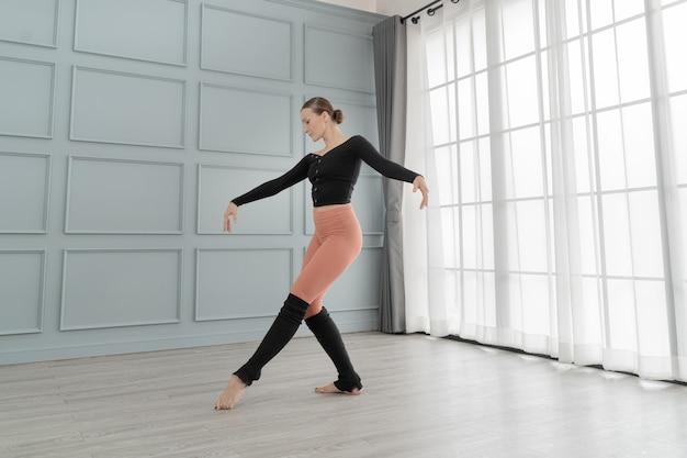 Het portret van vrouwenballetdanser presteert in studiohuis. hedendaagse danseres. opleiding klassiek balletdanser. mooie sierlijke ballerina oefenballet bij muur en raam lichte hal.