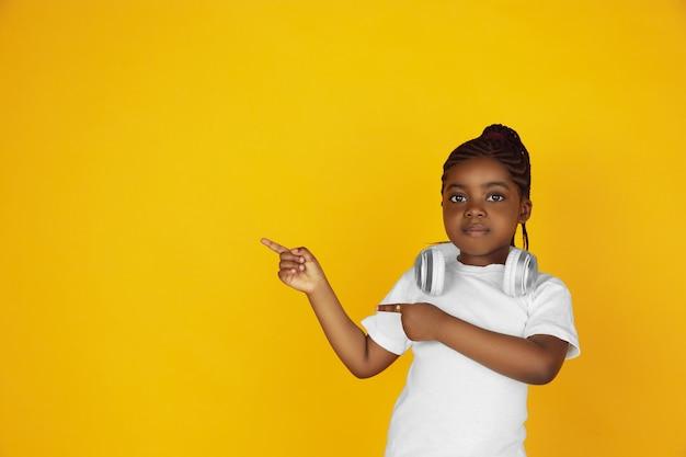 Het portret van weinig afrikaans-amerikaans meisje dat op gele studio wordt geïsoleerd