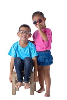 Het portret van weinig die jongen en meisje is kleurrijke die t-shirt met glazen op wit worden geïsoleerd