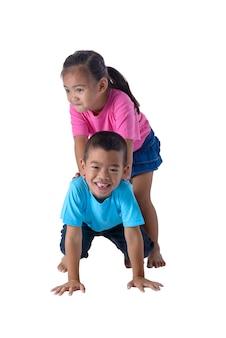 Het portret van weinig jongen en meisje is kleurrijke die t-shirt met glazen op witte achtergrond worden geïsoleerd