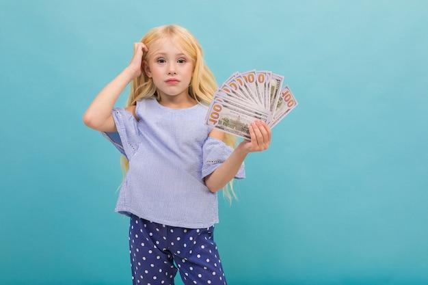 Het portret van weinig kaukasisch meisje in blauw t-shirt met lang blond haar houdt geld dat op blauwe achtergrond wordt geïsoleerd