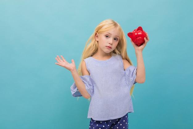 Het portret van weinig kaukasisch meisje in blauwe t-shirt met lang blond haar houdt rode die varkensspaarpot op blauwe achtergrond wordt geïsoleerd