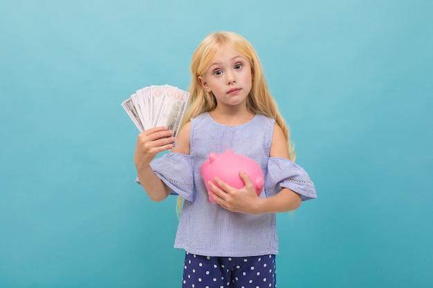Het portret van weinig kaukasisch meisje in blauwe t-shirt met lang blond haar houdt roze die varkensspaarpot op blauwe achtergrond wordt geïsoleerd