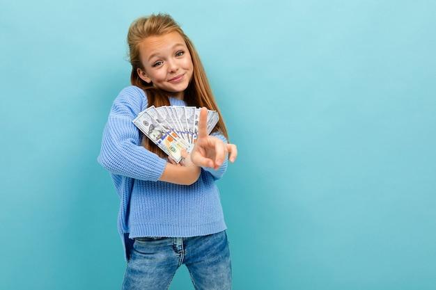 Het portret van weinig kaukasisch meisje met lang browhaar in blauwe hoody houdt heel wat geld dat op blauwe achtergrond wordt geïsoleerd