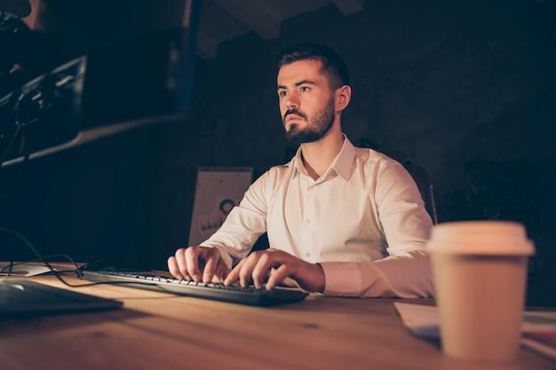 Het portret van zakenman zit het werk van het lijstbureau op computer