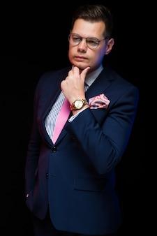 Het portret van zekere knappe zakenman die zijn hand houden dichtbij baard op zwarte achtergrond met dient zak in