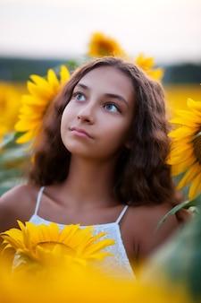Het portretgezicht van het tienermeisje op zonnebloemengebied.