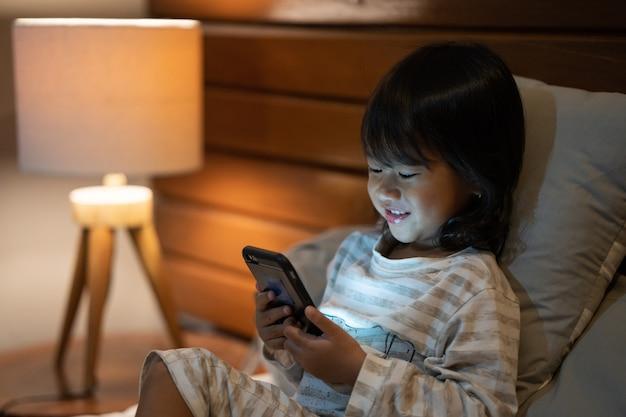 Het portretmeisje geniet van bekijkend video met een smartphone
