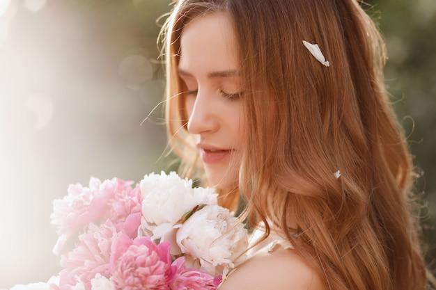 Het portretmodel van de close-up met bloemen in de zomer bij zonsondergang.