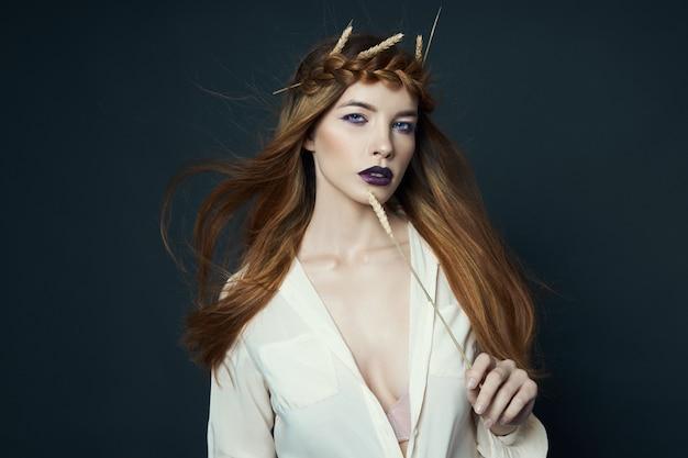 Het portretvrouw van de schoonheid met vlecht op haar hoofd en oren van tarwe. heldere donkere lippenstift en oogmake-up, gladde gezichtshuid. haar wapperen in de wind, tarwe in mooie handen meisje