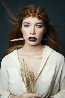 Het portretvrouw van de schoonheid met vlecht op haar hoofd en oren van tarwe. heldere donkere lippenstift en oogmake-up, gladde gezichtshuid. haar wapperen in de wind, tarwe in mooie handen vrouw