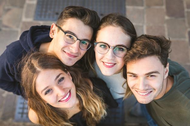 Het portretzitting van tienervrienden samen op een muur in de stad