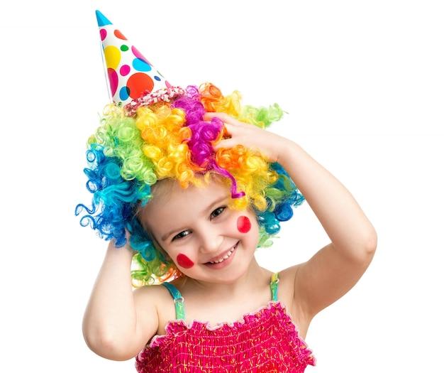 Het positieve die meisje stelt in clownpruik op witte achtergrond wordt geïsoleerd
