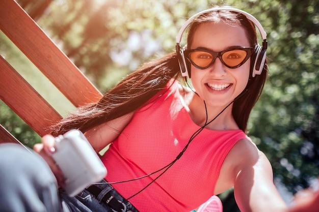 Het positieve en gelukkige meisje in rare glazen neemt selfie. zij lacht. meisje luistert naar muziek via een koptelefoon.