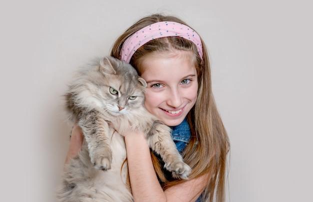 Het positieve meisje spelen met kat op grijs