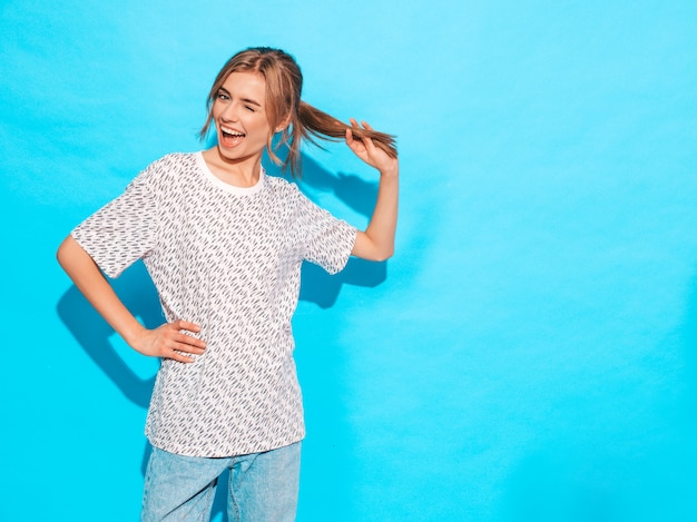 Het positieve vrouwelijke glimlachen. het grappige model stellen dichtbij blauwe muur in studio. het spelen met haar en knipoogt