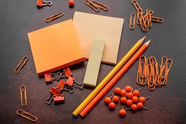 Het potlood, paperclips en vellen voor tekens liggen op een bureaublad